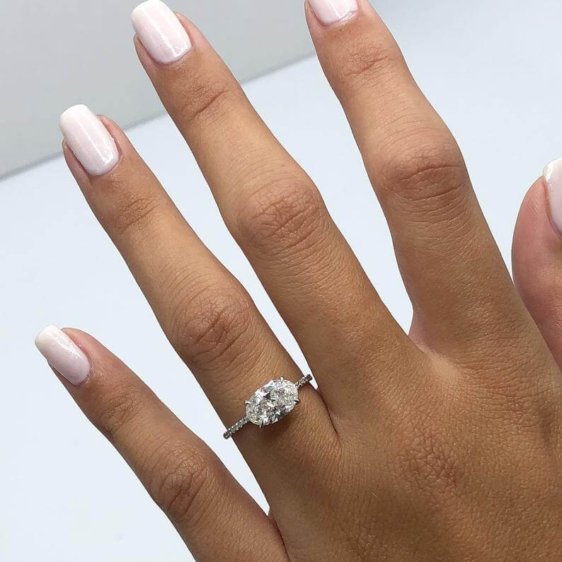East west oval shape engagement ring worn on finger