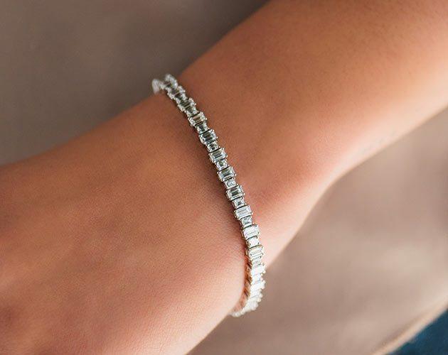 Emerald cut diamond bracelet on bride's hand