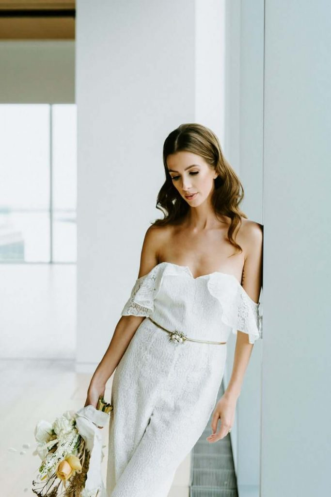 Bride wearing frilly bridal jumpsuit