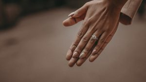 Girl's hand wearing engagement ring