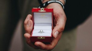 Man holding lab created diamond engagement ring in a red box