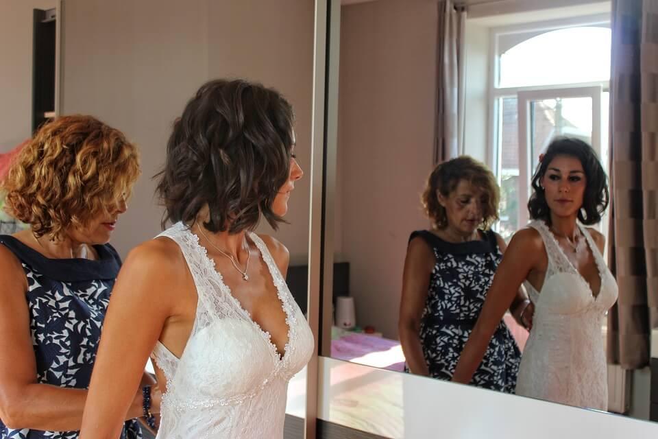 Mom helping bride getting dressed for wedding day