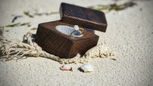 Oval shape diamond engagement ring in wooden box on sand