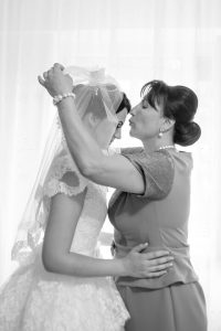 Mom kissing bride in the forehead