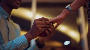 Man putting round shape diamond engagement ring on her finger