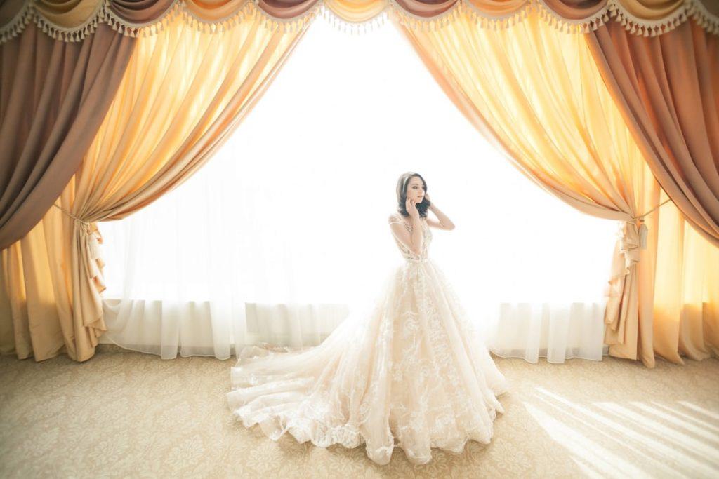 Bride accessorizing her wedding dress