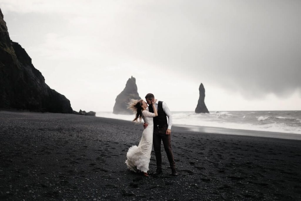 Bride and groom kissing at the beach