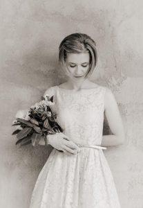 Bride in white dress holding flower