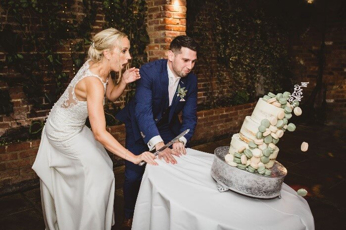 The cake topples to the ground second after the newlywed couple have cut into it