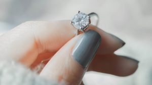 Woman holding moissanite engagement ring