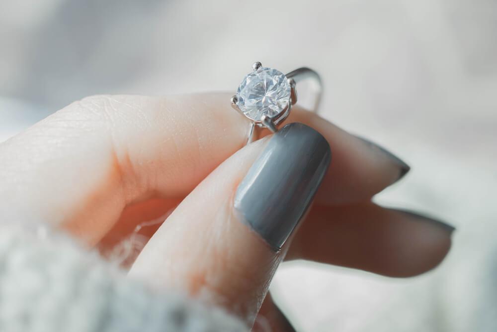 Woman holding moissanite engagement ring