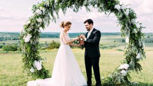 Bride and groom under wedding arch