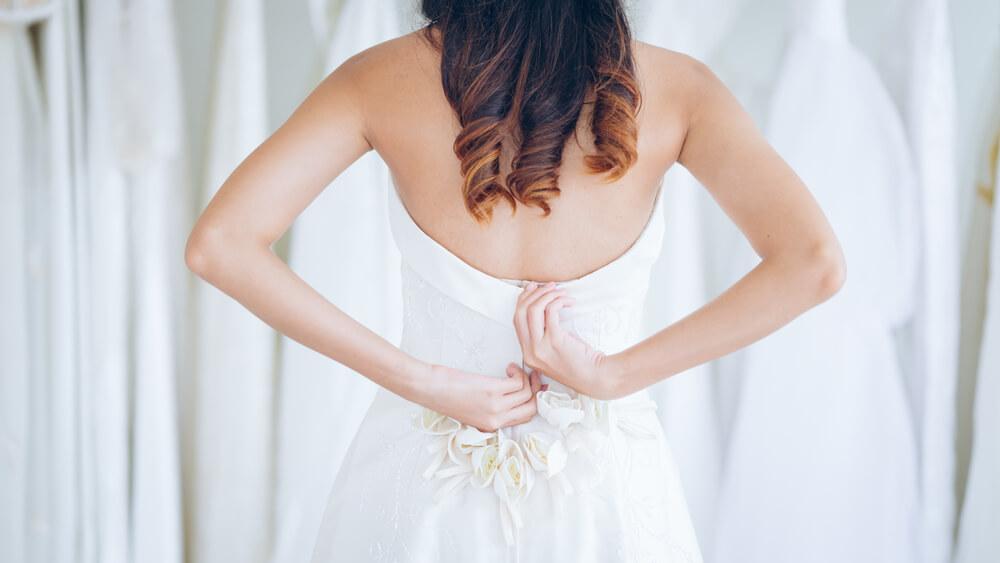 Bride considering her wedding dress when buying bridal underwear