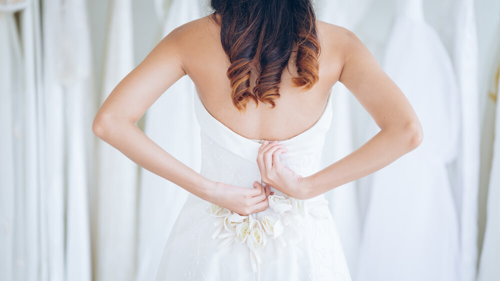 Bride considering her wedding dress when buying bridal underwear