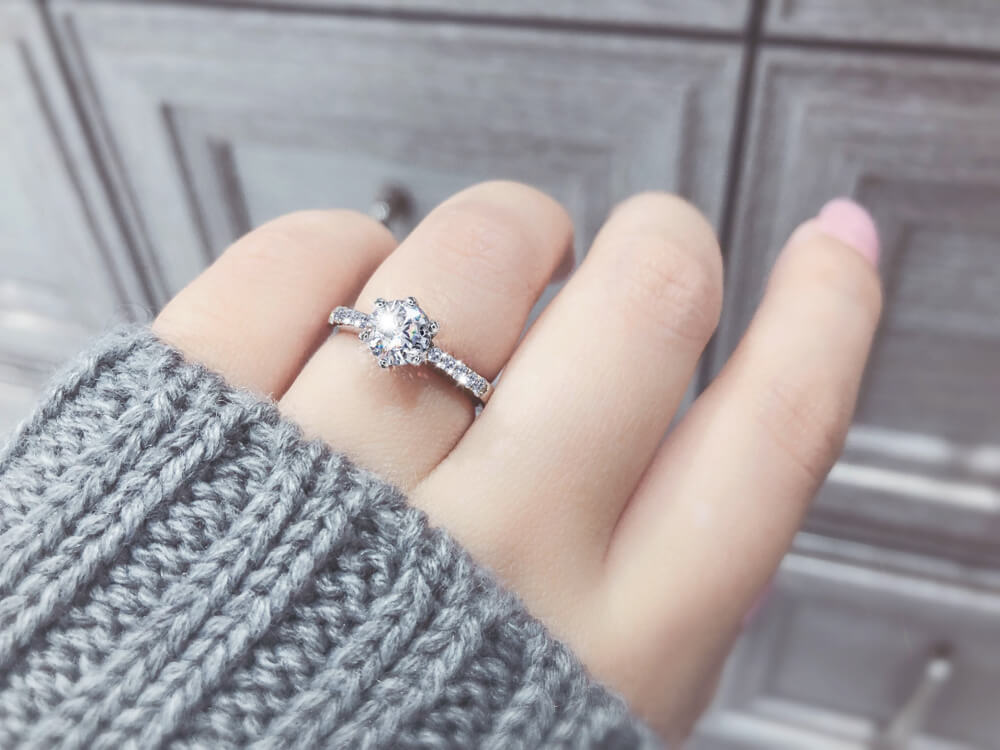 Girl wearing a gemstone that look like diamond in her engagement ring