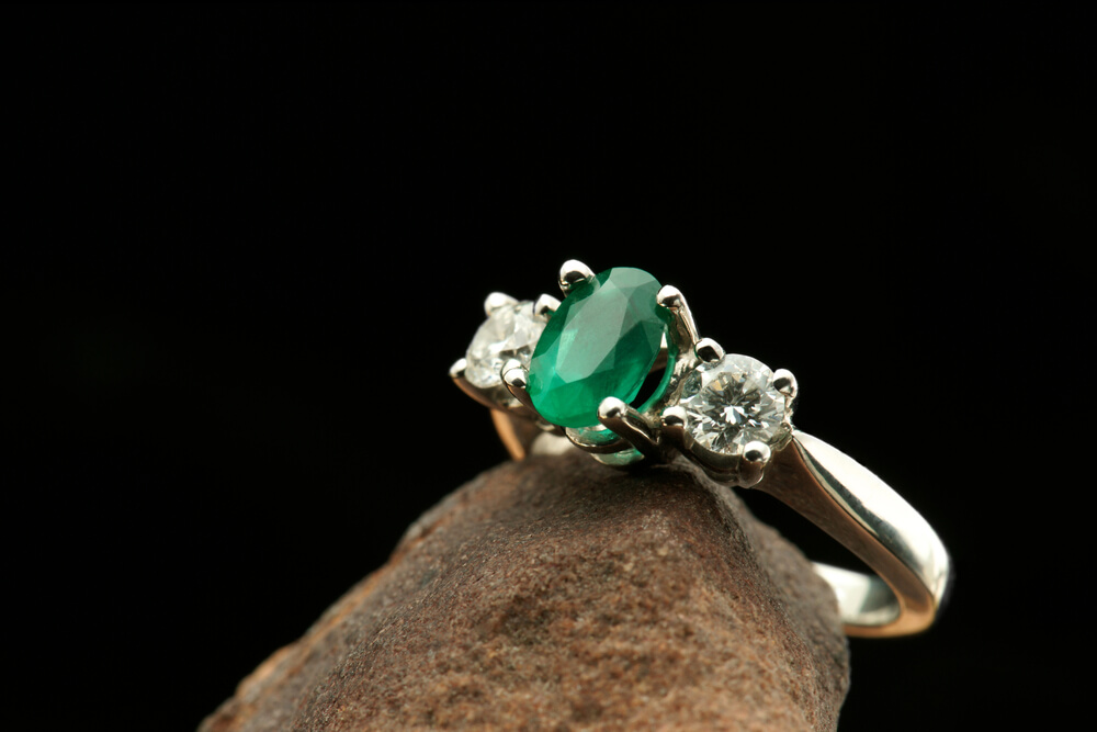 Green emerald with round diamonds as side stones engagement ring
