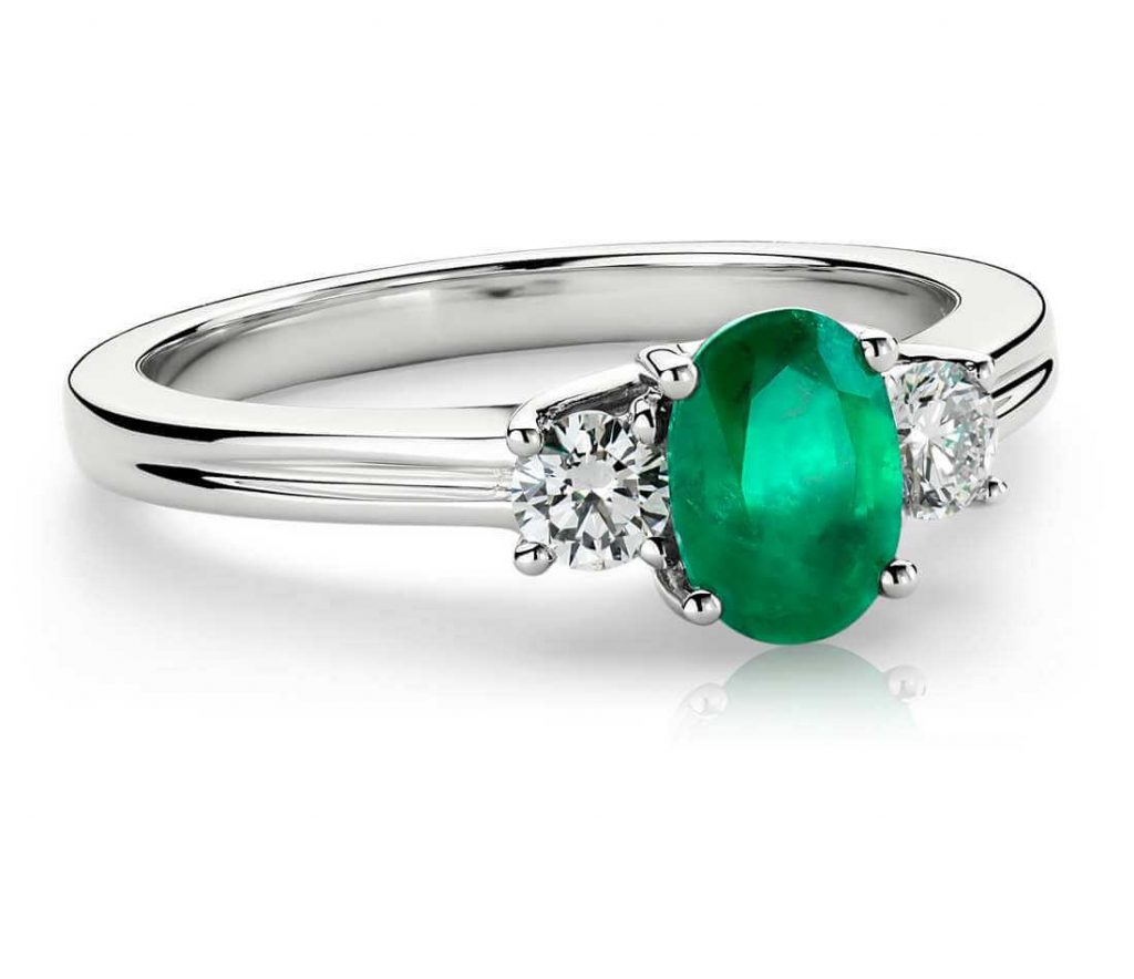 Oval shape emerald engagement ring with round shape diamond side stones