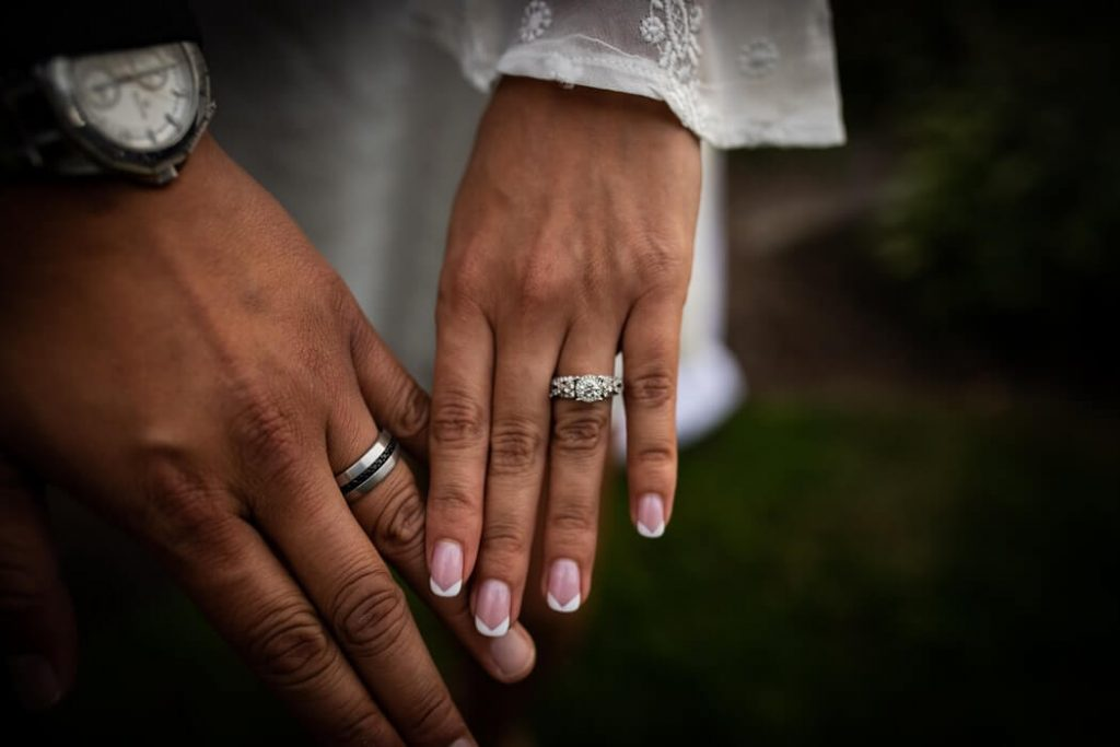 bride and grooms hands with white gold wedding rings close up