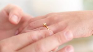 Woman wearing thin band engagement ring