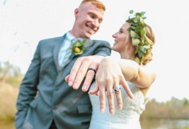 Groom wearing black wedding ring next to his bride