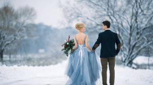 Bride wearing tulle dress holding groom's hand