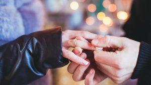 Man putting a cushion cut diamond ring on his girlfriend's hand