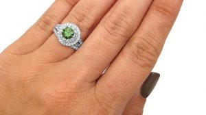 Green sapphire engagement ring on finger closeup