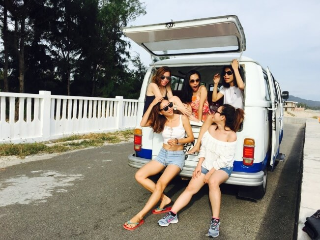 Girls sitting at the back of a van