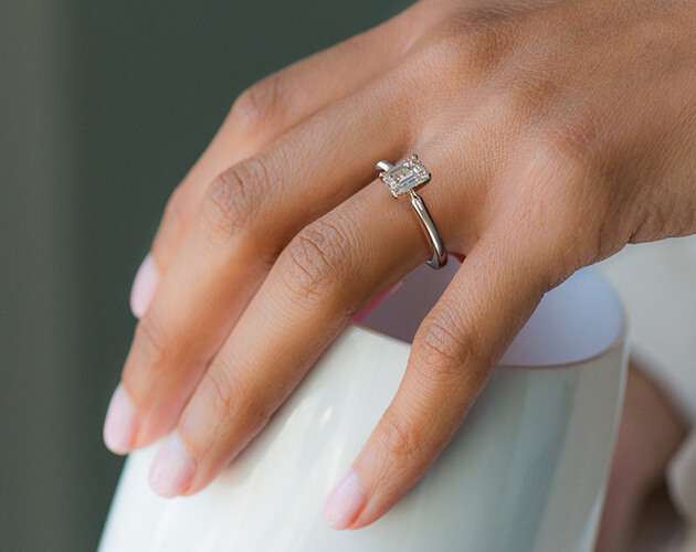 Solitaire emerald cut engagement ring on bride's finger