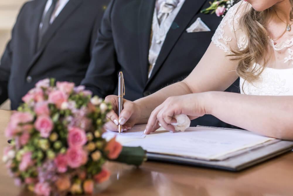 Couple signing wedding documents